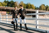 smiling equestrians in professional apparel walking near fence and talking at ranch