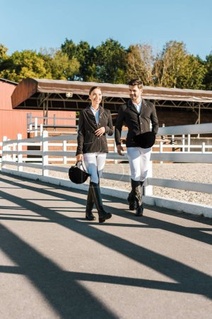 male and female equestrians in professional apparel walking near fence at ranch