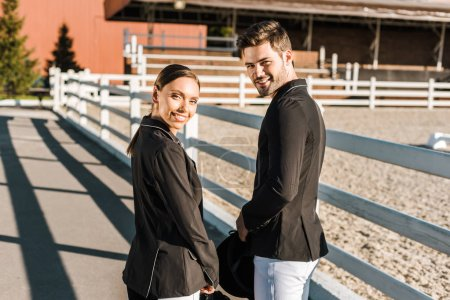 Photo for Back view of smiling equestrians in professional apparel standing at ranch and looking at camera - Royalty Free Image