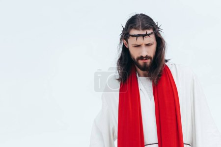 Jesus in robe, red sash and crown of thorns looking down against light sky