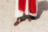 cropped image of Jesus in robe, red sash and sandals standing on sand in desert