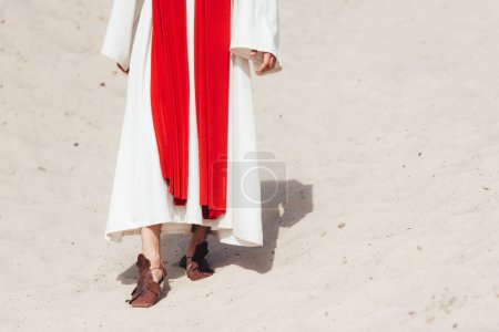 cropped image of Jesus in robe, red sash and sandals walking on sand in desert