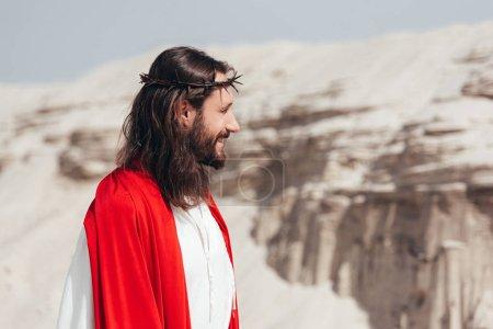 Foto de Vista lateral de sonriendo Jesús en Bata, faja roja y corona de espinas mirando lejos en el desierto - Imagen libre de derechos