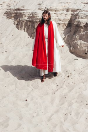 Jesus in robe, red sash and crown of thorns walking in desert