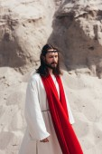 handsome Jesus in robe, red sash and crown of thorns walking with closed eyes in desert
