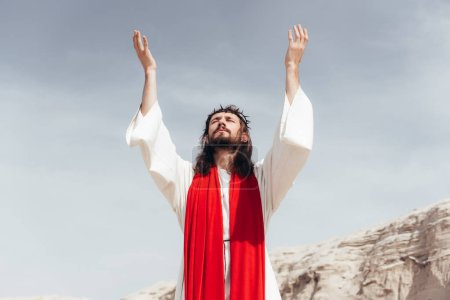 Photo for Jesus in robe, red sash and crown of thorns standing with raised hands and talking with god in desert - Royalty Free Image