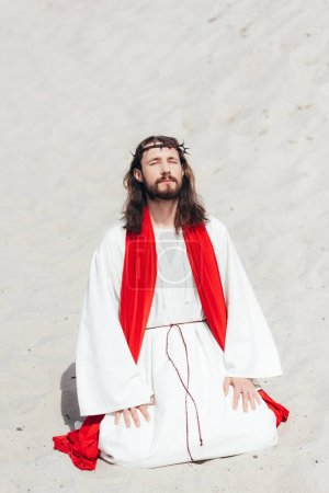 Photo for Jesus in robe, red sash and crown of thorns standing on knees with closed eyes and praying in desert - Royalty Free Image