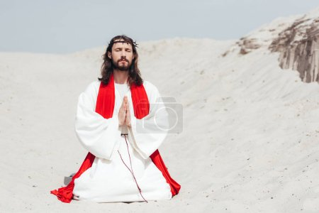 Photo for Jesus with closed eyes standing on knees on sand and praying in desert - Royalty Free Image