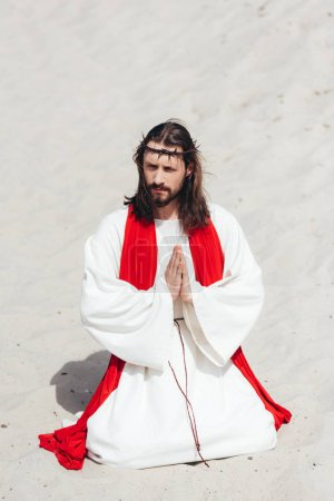 Jesus in robe, red sash and crown of thorns standing on knees and praying in desert, looking away
