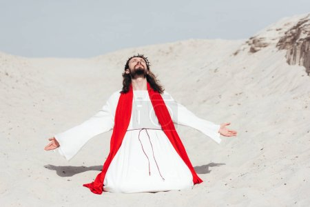 Photo for Jesus in robe, red sash and crown of thorns standing on knees with open arms in desert - Royalty Free Image