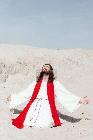 Photo pour Heureux Jésus en robe, écharpe rouge et Couronne d'épines, debout sur les genoux avec les bras ouverts dans le désert - image libre de droit