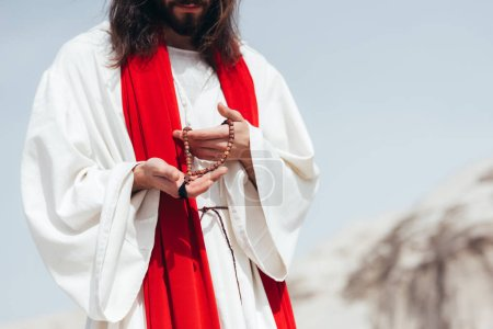 Photo pour Cropped image Jésus avec des cheveux longs en robe et écharpe rouge tenant Rosaire en bois dans le désert - image libre de droit
