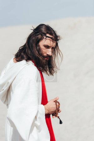 side view of Jesus in robe and red sash holding wooden rosary in desert