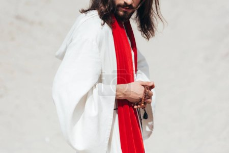 cropped image Jesus in robe and red sash holding rosary in desert