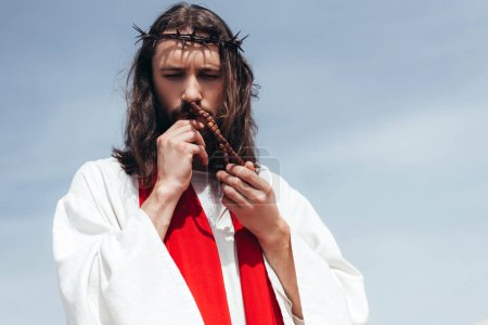 portrait of Jesus in robe, red sash and crown of thorns kissing rosary against blue sky