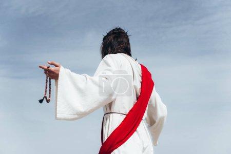 Photo pour Vue de Jésus en robe, écharpe rouge et Couronne d'épines tenant Rosaire contre le ciel bleu arrière - image libre de droit