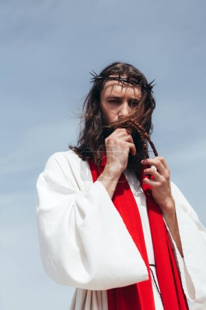 Jesus in robe, red sash and crown of thorns kissing rosary against blue sky
