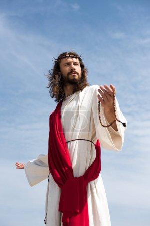 Photo pour Jésus en robe, écharpe rouge et la Couronne d'épines tenant Rosaire et debout, ouvrent les bras contre le ciel bleu - image libre de droit