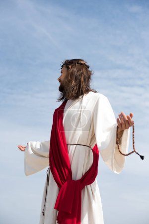 Jesus in robe, red sash and crown of thorns holding rosary and standing with open arms against blue sky, looking away