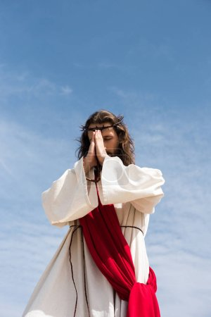 low angle view of Jesus Christ in robe, red sash and crown of thorns holding rosary and praying against blue sky