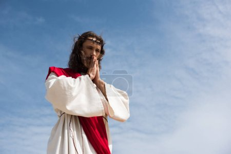 low angle view of Jesus in robe and red sash praying against blue sky