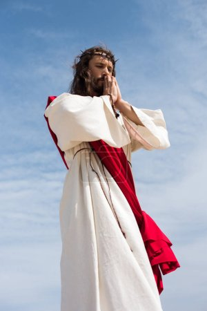 low angle view of Jesus in robe, red sash and crown of thorns holding rosary and praying against blue sky