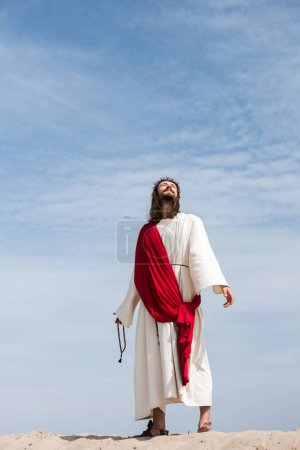 Jesus in robe, red sash and crown of thorns holding rosary and looking up in desert