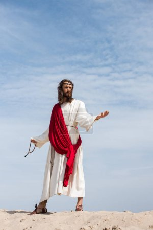 Jesus in robe, red sash and crown of thorns holding rosary and standing with open arms in desert