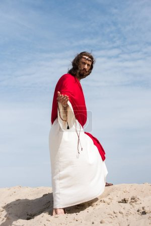 Jesus in robe, red sash and crown of thorns holding rosary and giving hand in desert