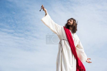 Photo pour Low angle view of Jesus in robe, red sash and crown of thorns holding rosary in raised hand against blue sky - image libre de droit