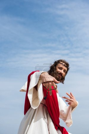 low angle view of Jesus having fun and showing two fingers with rosary against blue sky