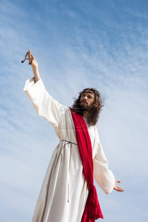low angle view of Jesus in robe, red sash and crown of thorns holding rosary and standing with open arms against blue sky