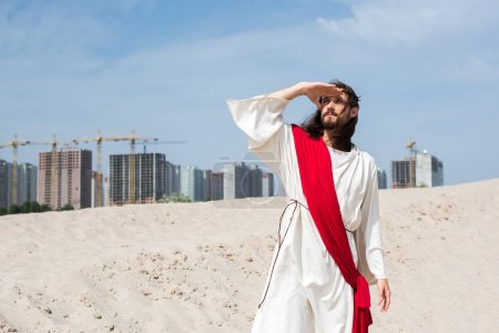 Jesus in robe, red sash and crown of thorns standing on sand and looking up with buildings on background