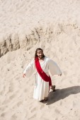 high angle view of Jesus in robe, red sash and crown of thorns walking on sand in desert