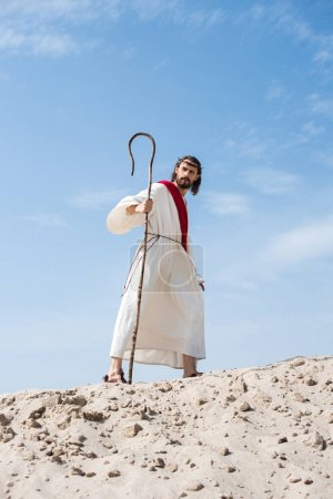 Jesus in robe, red sash and crown of thorns walking on sandy hill with staff in desert