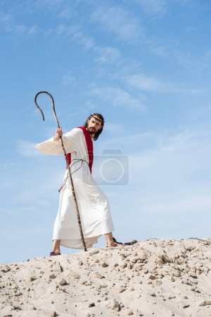 low angle view of Jesus in robe, red sash and crown of thorns walking on sandy hill with staff in desert