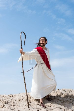 smiling Jesus in robe, red sash and crown of thorns standing with wooden staff in desert