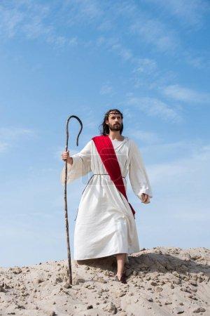 Photo pour Jésus en robe, écharpe rouge et Couronne d'épines, debout sur la colline de sable avec le personnel en bois dans le désert - image libre de droit
