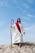 Jesus in robe, red sash and crown of thorns standing on sandy hill with wooden staff in desert