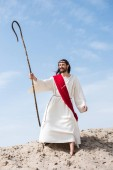 happy Jesus in robe, red sash and crown of thorns standing with wooden staff in desert and looking away