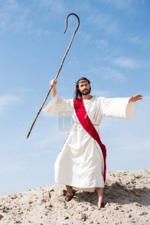 Jesus in robe, red sash and crown of thorns swinging wooden staff in desert