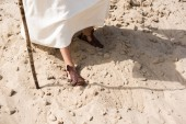 cropped image of Jesus in robe and sandals walking on sand with wooden staff in desert