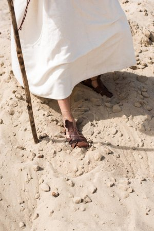 cropped image of Jesus in robe and sandals walking in desert with wooden staff