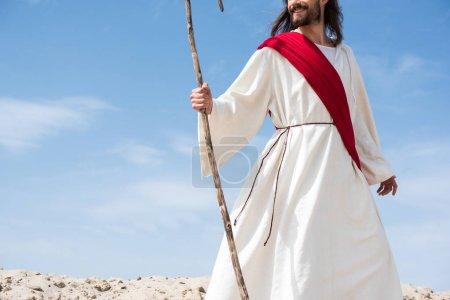 Photo pour Cropped image de Jésus souriant en robe et permanente de l'écharpe rouge avec le personnel en bois dans le désert - image libre de droit
