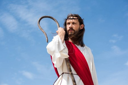 Jesus in robe, red sash and crown of thorns standing with wooden staff against blue sky and looking away