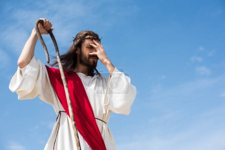 Photo pour Jésus en robe, écharpe rouge et Couronne d'épines permanent avec le personnel en bois dans le désert et touchant front - image libre de droit