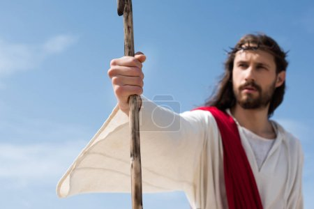 Photo for Selective focus of Jesus in robe, red sash and crown of thorns holding wooden staff in desert - Royalty Free Image