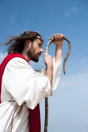 Photo pour Vue de côté de Jésus dans la robe et la Couronne d'épines, appuyé sur un bâton en bois contre le ciel bleu - image libre de droit