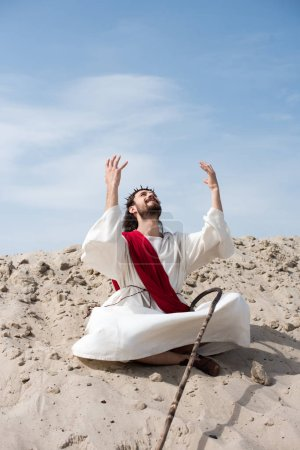 cheerful Jesus in robe and red sash sitting in lotus position with raised hands and talking with god on sand in desert