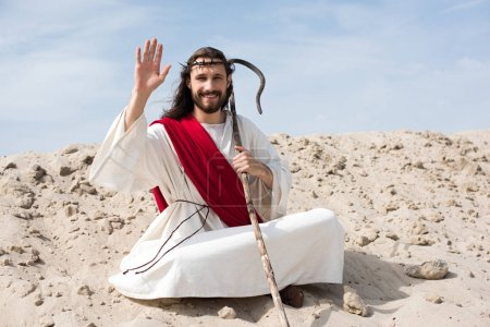 Jesus in robe, red sash and crown of thorns sitting in lotus position on sand in desert and waving hand